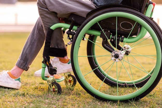 A disabled man is sitting in a wheelchair he holds his hands on the wheel high quality photo