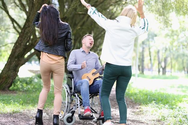 장애인 남자는 공원에서 기타를 연주하고 두 여자는 친구 옆에서 춤을 추고 지원합니다.