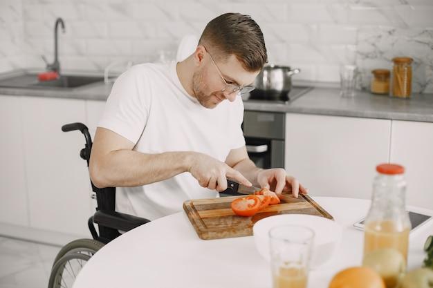 Человек с ограниченными возможностями готовит еду на кухне. нарезка овощей.