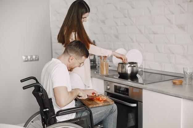 障害者の男性がキッチンで食事を準備しています。野菜を切る。