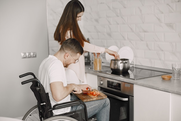 Disabled man preparing food in kitchen. cutting vegetables.