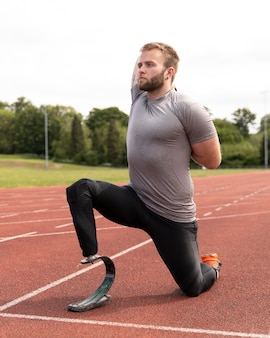 Disabled man on running track stretching full shot