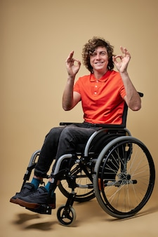 Disabled man showing ok gesture, curly caucasian male smiling, doesn't give up, isolated portrait
