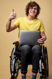 障害者の男性は、ラップトップを持って車椅子に座って、オンラインで作業しています。ベージュの背景のスタジオで隔離のカメラでカジュアルな服装で笑顔の巻き毛の若い男性