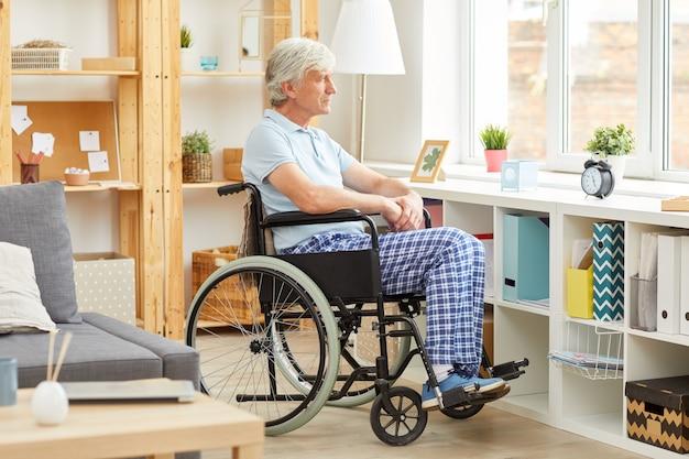 障害者の男性が自宅で座っています。