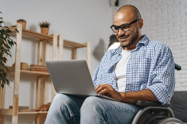 Человек-инвалид, сидящий в инвалидной коляске и использующий ноутбук