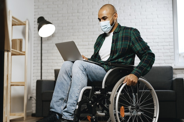 Disabled man sitting in a wheelchair and using laptop with face mask on