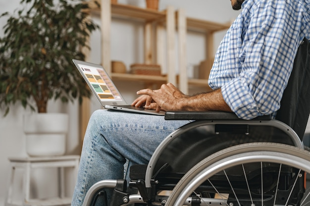 Disabled man sitting in a wheelchair and using laptop