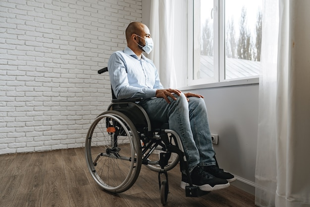 Disabled man sitting in a wheelchair and wearing face mask