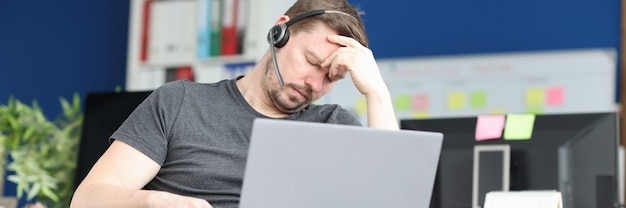 Disabled man sleeping in wheelchair with laptop on his lap resilience at work concept