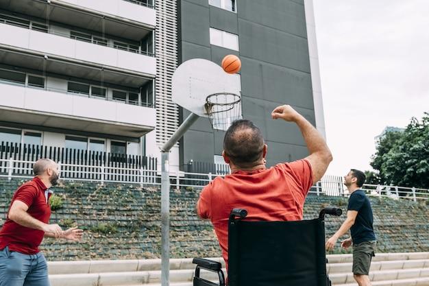 두 친구와 함께 바구니에 던지는 장애인 된 남자