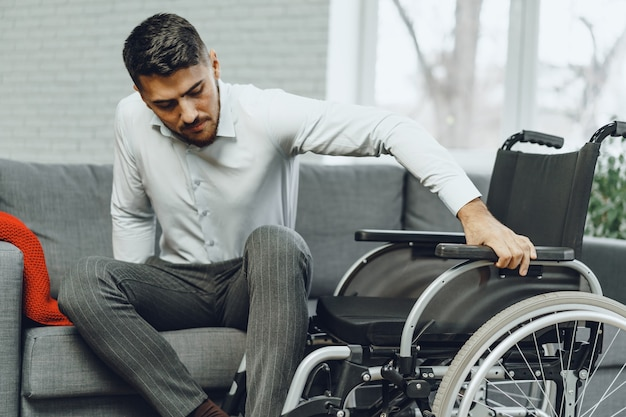 Disabled man tries to sit down on a sofa from wheelchair close up