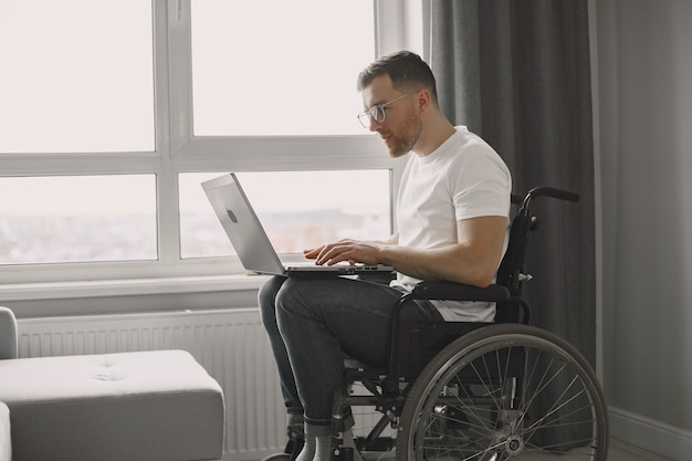 Disabled man using laptop. cheerful handsome man stay at home and work remotely.