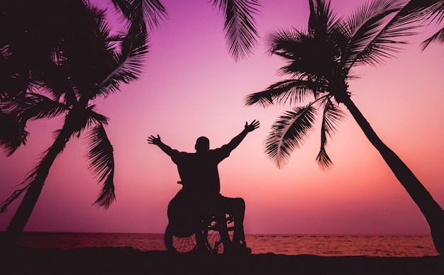 Disabled man in a wheelchair on the beach. silhouette at sunset.