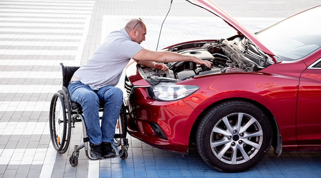 Disabled man in wheelchair check engine his car at parking
