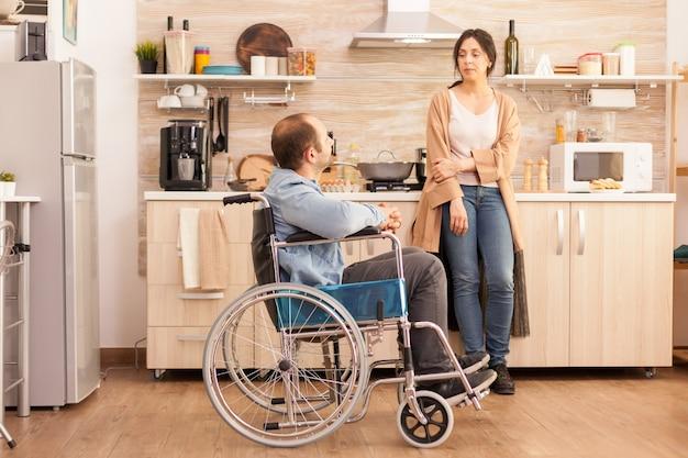 Uomo disabile in sedia a rotelle che ha una conversazione con la moglie in cucina mentre prepara il cibo. disabile paralizzato uomo handicappato con disabilità motoria che si integra dopo un incidente.