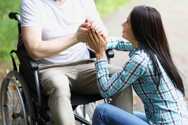 Disabled man in wheelchair holding woman hands in park closeup