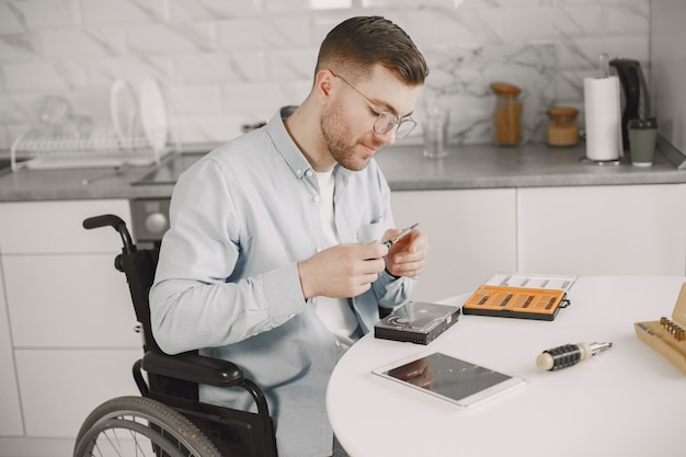 Disabled man on wheelchair like repairing. staying at home, hobbies.