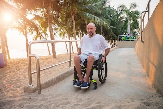 Disabled man in a wheelchair moves on a ramp to the beach.