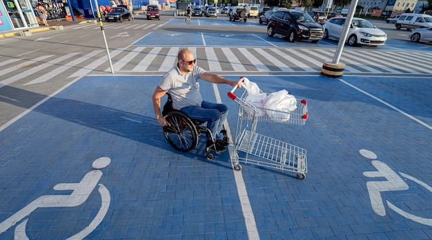 Disabled man in wheelchair pushing cart in front of himself at supermarket parking