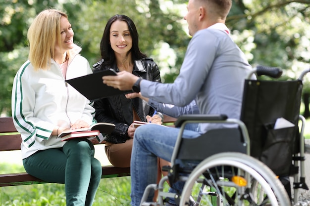 Disabled man in a wheelchair shows results of his work as designer on tablet to women in park