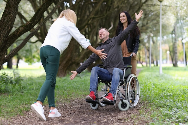 Disabled man in wheelchair walking in park with nurse and hugging his girlfriend full life of