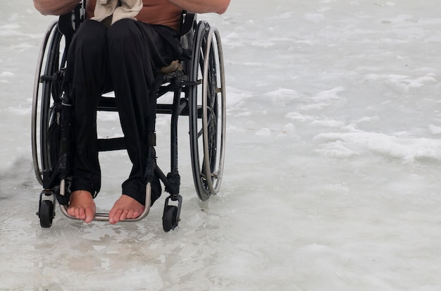 A disabled man in a wheelchair in the winter is going to swim in the cold water in the ice