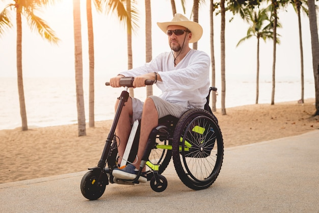 Disabled man in a wheelchair with electric scooter on the beach