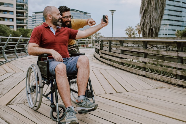 A disabled man on wheelchair with his assistant looking to a mobile phone