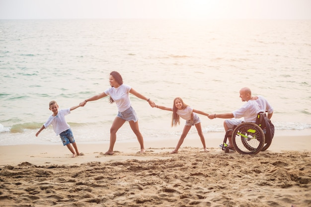 Disabled man in a wheelchair with his family on the beach.