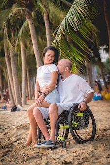 Disabled man in a wheelchair with his wife on the beach.