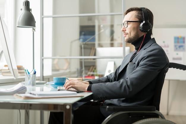 テーブルで働いている障害者の男