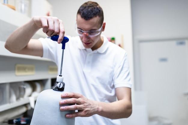 생산 의수 말단 부품을 위해 절단 수술실에서 일하는 장애인.