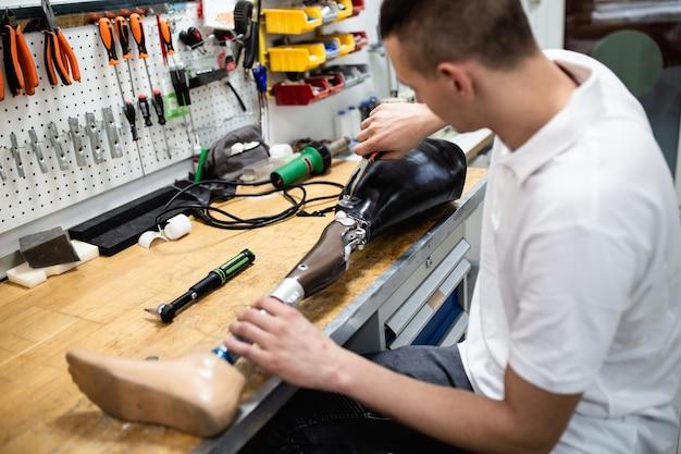 생산 보철 사지 부품을 위해 절단 된 상점에서 일하는 장애인.
