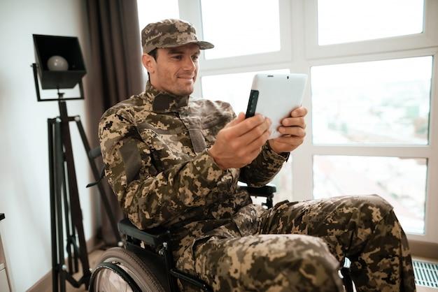 장애인 된 군 남자 휠체어에 태블릿을 사용