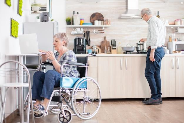 휠체어를 탄 장애인 노부인이 부엌에서 노트북 작업을 하고 있습니다. 현대 통신 온라인 인터넷 웹 기술을 사용하는 마비된 노인 노인.