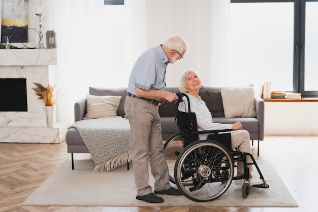 Disabled old woman on wheel chair  senior couple at home partner coming back from hospital