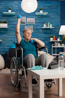 Disabled old woman in wheelchair raising arm training muscles resistance using dumbbells