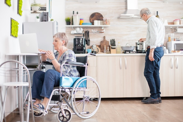 Disabled old woman in wheelchair working on laptop in kitchen. paralyzed handicapped old elderly person using modern communication online internet web techonolgy.