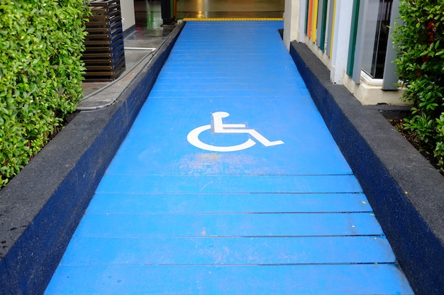 Disabled parking sign on slope pathway.