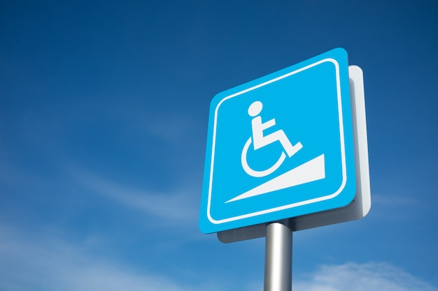 Disabled parking signage with blue sky.