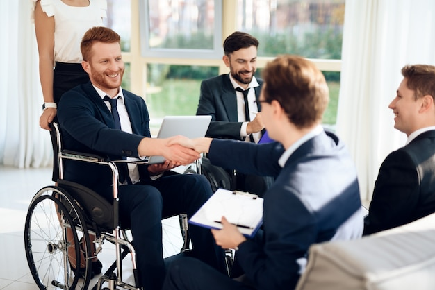 Disabled people in business suits in a bright room.