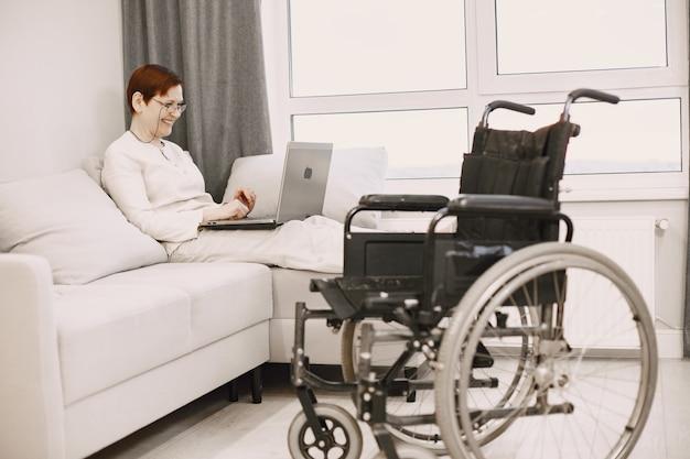障害者の生活。成熟した女性はラップトップでソファに横になりました。