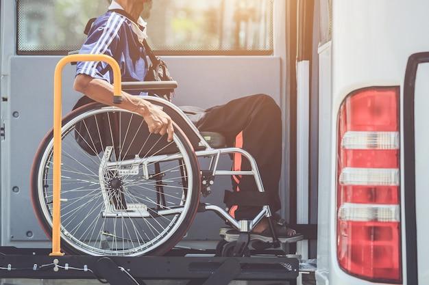 Инвалиды, сидящие на инвалидной коляске и идущие на общественный автобус Premium Фотографии