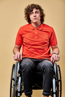 Disabled person on wheelchair is looking upset, has no meaning of life, suffer from disability. portrait. isolated beige background