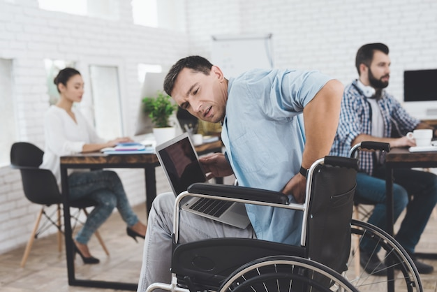 Disabled person in the wheelchair works in the office.