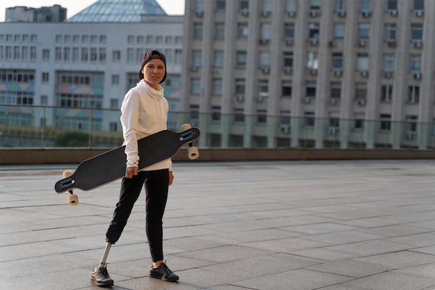 屋外でスケートボードを持っている障害者