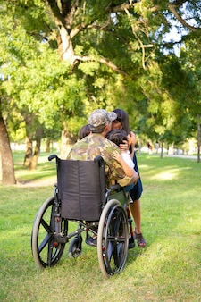 Disabled retired military father returning home, hugging and kissing wife and two kids. back view. veteran of war or returning home concept