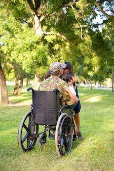 Padre militare in pensione disabile che torna a casa, abbraccia e bacia moglie e due figli. vista posteriore. veterano di guerra o concetto di ritorno a casa