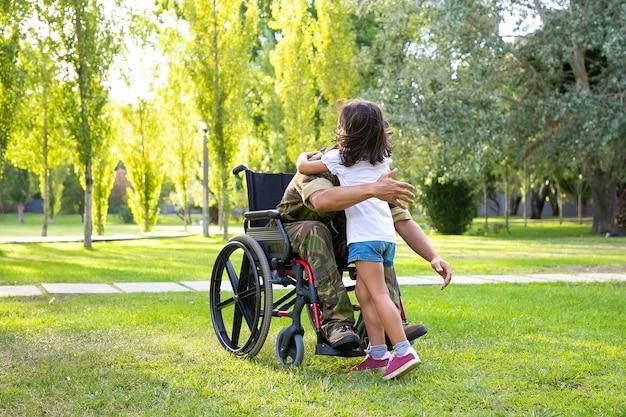 Uomo militare in pensione disabile che incontra e abbraccia piccola figlia nel parco. veterano di guerra o concetto di ritorno a casa